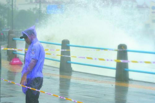 """图片说明:9日,""""利奇马""""在浙江省温岭市石塘镇金沙滩海边掀起巨浪。11日,一名协警在青岛海边维持秩序。"""