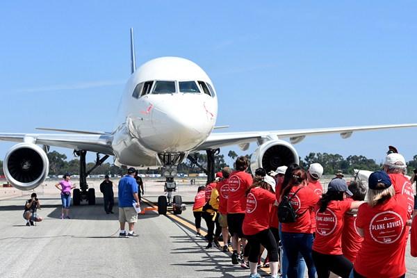 美国南加州众人齐心协力拉飞机 场面壮观