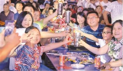 8月16日,消费者在重庆市渝北艺术欢享夜市集现场举杯欢聚。新华社记者 王全超摄