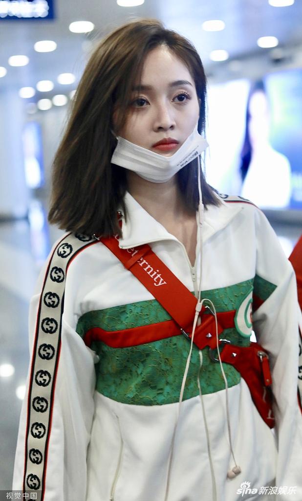 吴宣仪精致装扮半戴口罩现身机场 眼神呆萌面带倦容