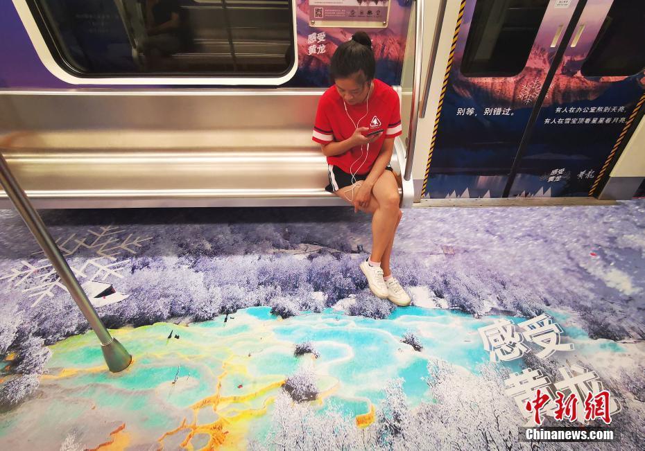 """9月9日,四川成都,地铁车厢内的美景吸引乘客。当日,随着一声鸣笛的响起,四川黄龙景区""""瑶池仙境号""""主题地铁列车正式上线始发,该列车将黄龙自然美景融进车厢,让人身临其境。中新社记者 刘忠俊 摄"""