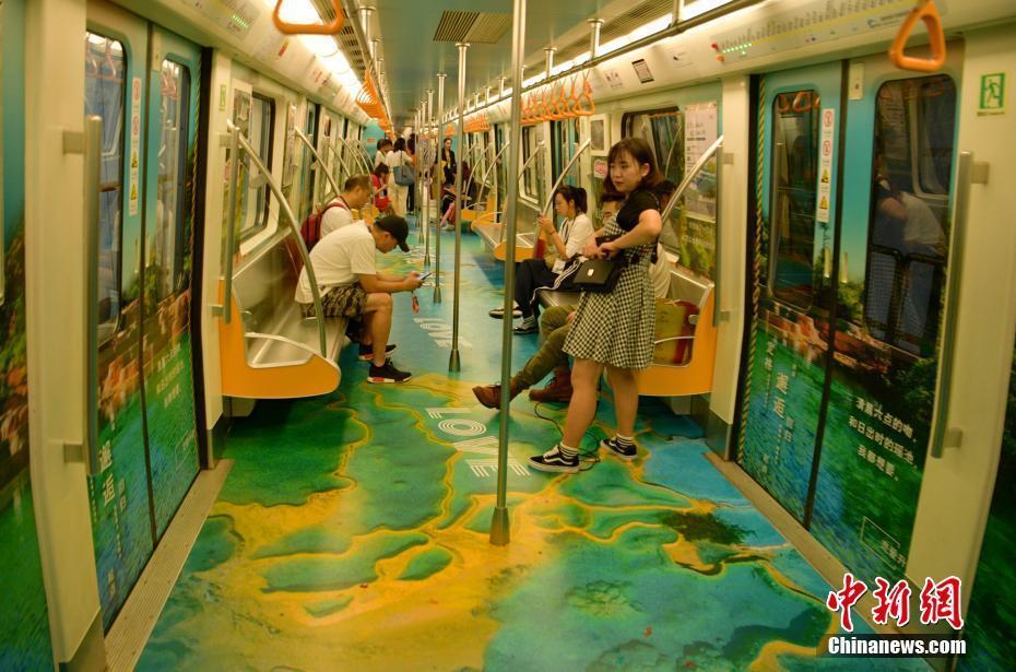 """9月9日,四川成都,漂亮的""""瑶池仙境号""""主题地铁列车引乘客关注。当日,随着一声鸣笛的响起,四川黄龙景区""""瑶池仙境号""""主题地铁列车正式上线始发,该列车将黄龙自然美景融进车厢,让人身临其境。中新社记者 刘忠俊 摄"""