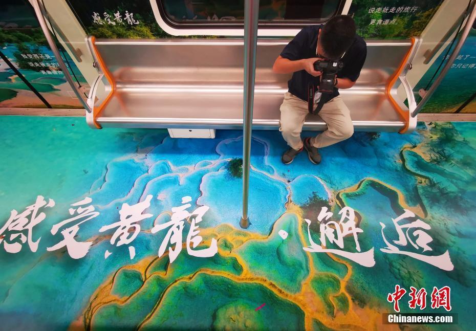 """9月9日,四川成都,一名攝影愛好者拍攝主題列車。當日,隨著一聲鳴笛的響起,四川黃龍景區""""瑤池仙境號""""主題地鐵列車正式上線始發,該列車將黃龍自然美景融進車廂,讓人身臨其境。中新社記者 劉忠俊 攝"""