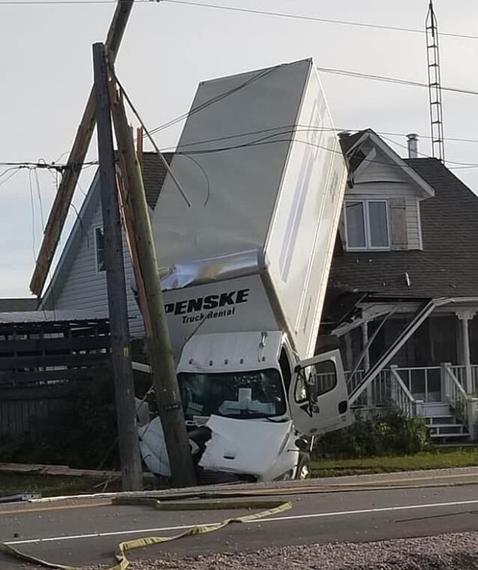 加拿大一卡车失控撞上电线杆后翻转 落在居民屋顶上