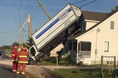 卡车失控撞上�电线杆后翻转 落在居民屋顶上