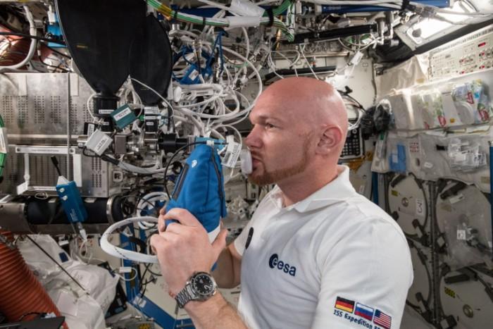 宇航员正在利用奇怪的小型科学机器进行呼吸测试