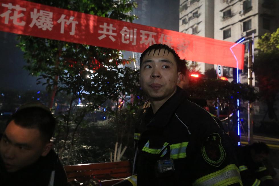 消防员摘下呼吸器给被困者,用湿浴巾捂口鼻继续施救