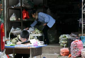 西安8岁男孩菜摊边写作业 妈妈边卖菜边辅导